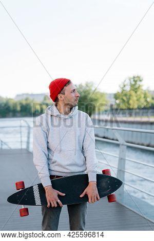 Stylish Hipster Man Skateboarder Holding Longboard Skating On Bridge On Sunset. Millennial Male Long