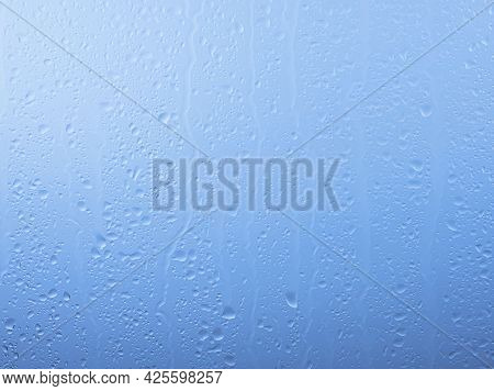 Close Up Raindrops And Water Runs On Glass Window Pane Surface Over Grey And Blue Sky Background On