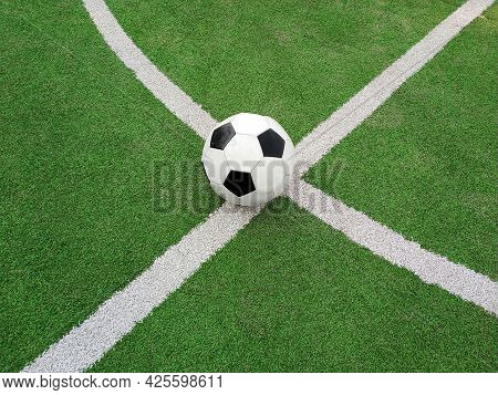 Close Up One Black And White Football Ball Over Green Artificial Turf Of Soccer Field Pitch With Whi