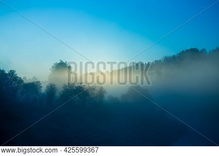 A Misty Sunrise Landscape Over The Small River Valley. Summertime Scenery Of Northern Europe.