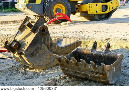 Two Large Excavator Buckets At The Construction Site, Tractor In The Background