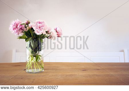 A Bunch Of Pastel Pink Peony With Green Leaves In Glass Vase On The Wooden Table Near White Wall Tex