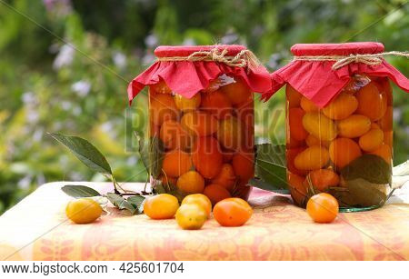 Marinated Cherry Tomatoes In Jars On A Table In The Garden, Closeup