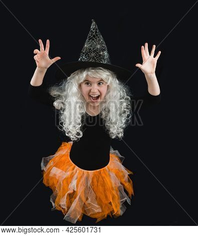 A Cheerful Girl In A White Wig And A Witch Costume Scares. Horror