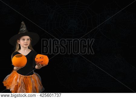 A Cheerful Girl With Long Hair And In A Witch Costume For Halloween Celebration Holds Out Two Jack P