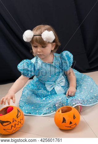 A Cheerful Toddler Girl In A Beautiful Blue Dress With Orange Pumpkins For Collecting Sweets