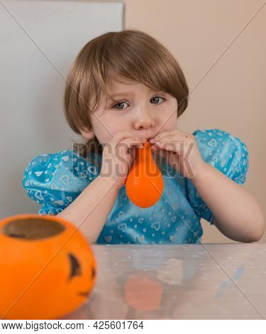 A Toddler Girl In A Blue Dress Inflates An Orange Balloon. There Is A Pumpkin For Sweets On The Tabl
