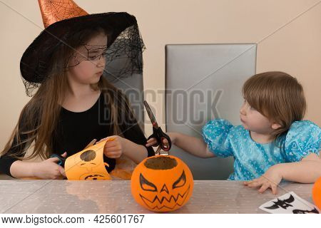 Two Girls Sisters In Costumes Of A Witch And Snow White Sitting At A Table Cut Out A Paper Garland F