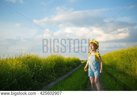 Cheerful Girl In A Yellow Hat In A Summer Field Laughs And Smiles. Joy, Sunny Weather, Holidays. A R