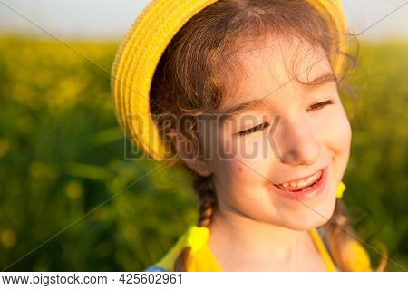 A Cheerful Girl In A Yellow Hat In A Summer Field Laughs. Carelessness, Joy, Sunny Weather, Holidays