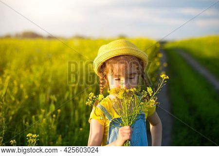 A Girl In A Yellow Summer Field Sniffs A Bouquet Of Flowers. Sunny Day, Holidays, Allergy To Floweri