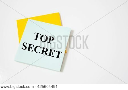 Top Secret Text Written On A White Notepad With Colored Pencils And A Yellow Background