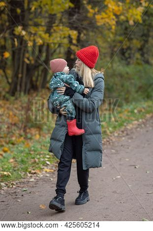 A Walk In The Park In A Toddler, Mom Carries A Child In Her Arms Along The Street, Warm Clothes For