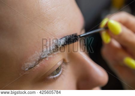 Beautician Making Depilation With Wax Strip Young Womans Eyebrows In Spa Center. Attractive Woman Ge