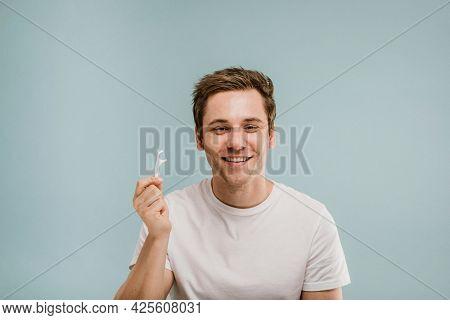 Cheerful man showing a dental floss pick