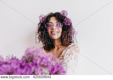 Indoor Portrait Of Carefree Black Girl Looking Away During Photoshoot With Flowers. Pleased African