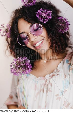 Jocund African Girl Posing With Alliums And Laughing. Indoor Shot Of Graceful Black Woman With Wavy