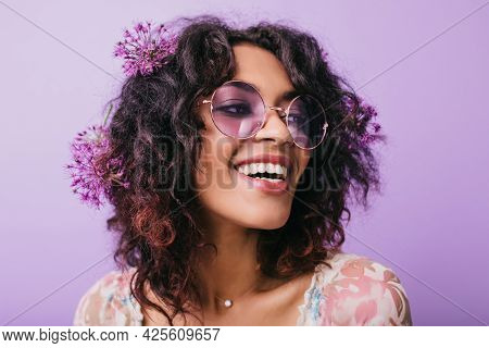 Close-up Photo Of Good-humoured African Lady With Flowers In Hair. Indoor Shot Of Laughing Black Gir