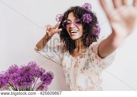 Enthusiastic African Girl In Stylish Dress Making Selfie With Alliums. Spectacular Black Young Woman
