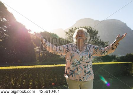 Happy senior caucasian woman with arms outstretched in sunny garden. luxury retirement lifestyle, spending time alone at home.