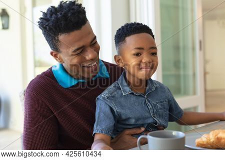 Happy african american son sitting on father's knee at table during breakfast and smiling. family enjoying quality free time together.