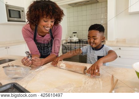 Happy african american mother with son baking in kitchen, rolling dough. family enjoying quality free time together.