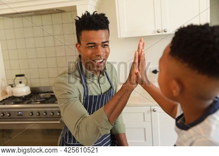 Happy african american father and son high fiving in kitchen before cooking. family enjoying quality free time together.
