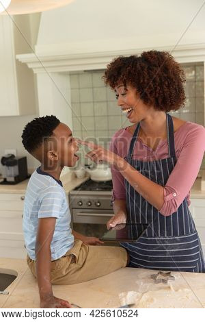 Happy african american mother with son baking in kitchen, having fun and using tablet. family enjoying quality free time together.