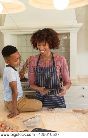 Happy african american mother with son baking in kitchen, using tablet. family enjoying quality free time together.