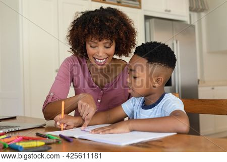 Happy african american mother and son doing homework at home smiling. family domestic life, spending time learning together at home.