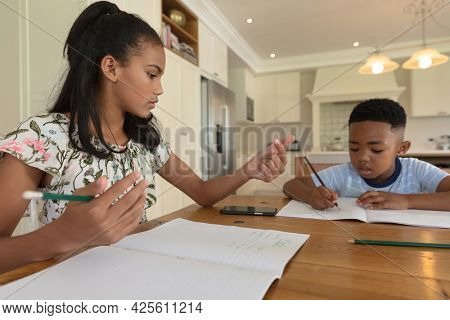 African american brother and sister doing homework at home, sitting at table. family domestic life, spending time working together at home.