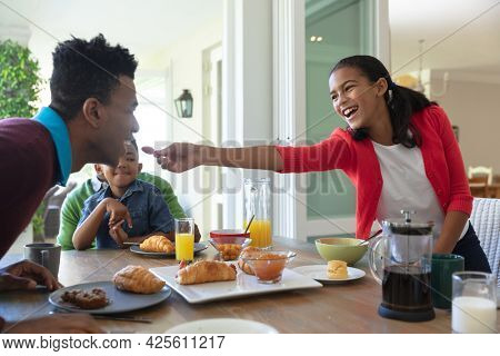 Happy african american son and father sitting at table during breakfast, daughter feeding him. family enjoying quality free time together.