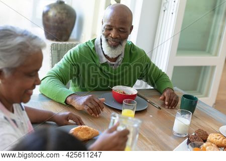Happy african american family sitting at table smiling during breakfast and smiling. family enjoying quality free time together.