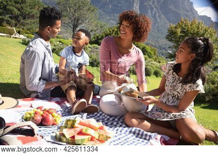 Happy african american couple with son and daughter outdoors, having picnic in sunny garden. family enjoying quality free time together.
