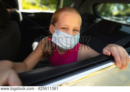 Portrait of caucasian girl wearing face mask and sitting in car. medical precautions, lifestyle during covid 19 pandemic.