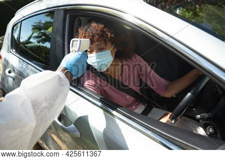Medical worker wearing ppe suit taking temperature of african american woman sitting in car. medical precautions, lifestyle during covid 19 pandemic.