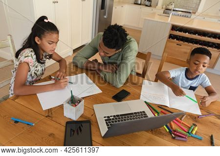 Happy african american father with daughter and son doing homework at home smiling. family domestic life, spending time learning together at home.