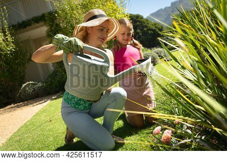 Happy caucasian mother and daughter outdoors, gardening on sunny day. family enjoying quality free time together.