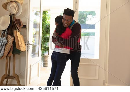 Happy african american father with daughter back from work smiling and embracing at home. family enjoying quality free time together.