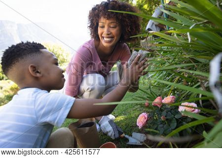 Happy african american mother with son outdoors, gardening on sunny day. family enjoying quality free time together.