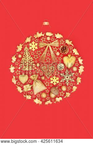 Decorative Christmas abstract round tree bauble decoration with gold objects and stars on red background. Flat lay, top view, copy space. Design concept for the festive season.