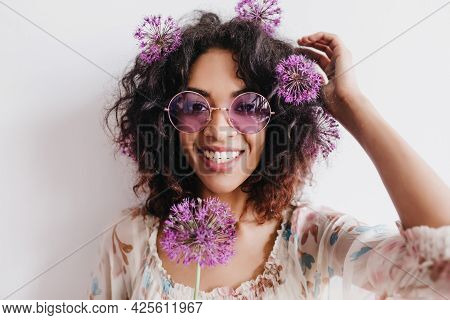 Emotional Black Woman Laughing To Camera While Posing With Purple Flowers. Indoor Shot Of Adorable A