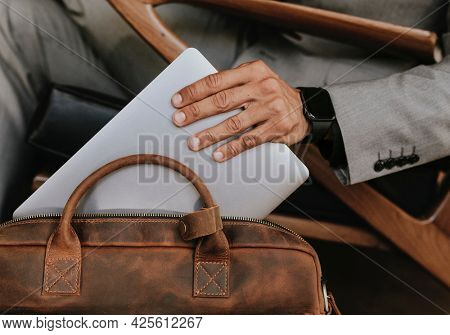 Classy businessman putting his laptop in his brown leather bag