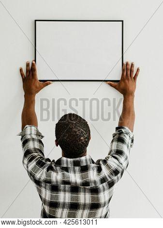 Curator hanging art frame mockup on the wall
