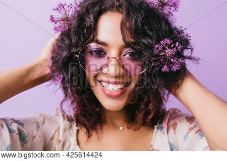 Close-up Portrait Of Pleasant African Girl With Wavy Black Hair. Indoor Photo Of Smiling Female Mode