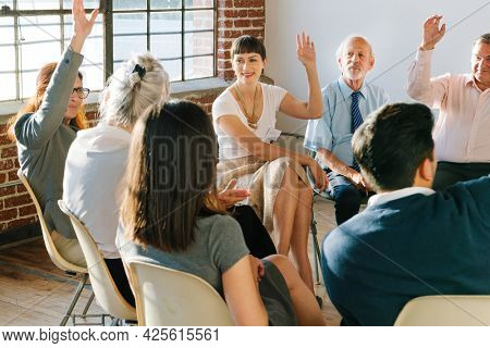 People raising hands to ask