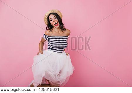 Good-humoured Brunette Girl Playfully Posing On Pastel Background. Studio Shot Of Ecstatic Young Wom