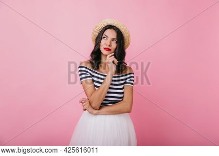 Elegant Girl With Tanned Skin Posing With Pensive Face Expression On Bright Background. Studio Photo