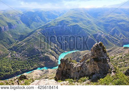 Tourist Girl On The Top Of A Cliff Against The Background Of The Sulak Canyon Surrounded By Mountain