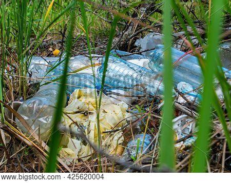Plastic And Polyethylene Household Waste In Green Grass. Plastic Bottle. Plastic Bag. Waste. Environ
